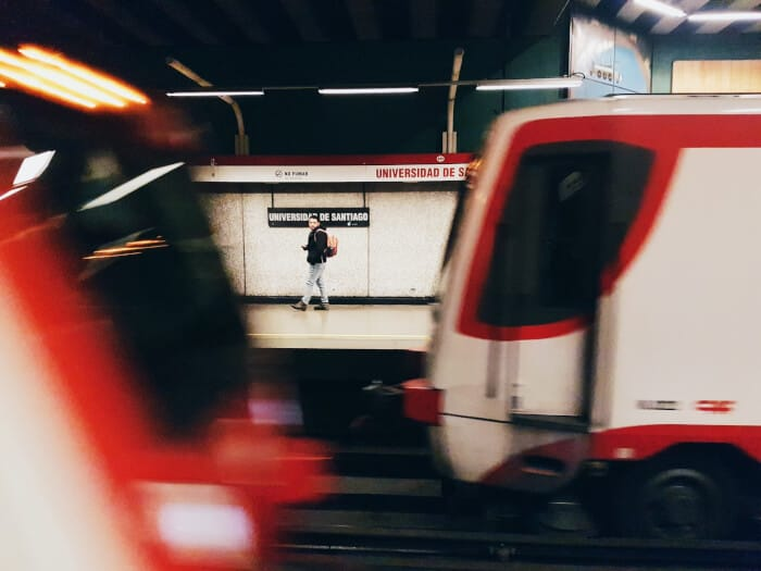 Red train with high speed and a man walking